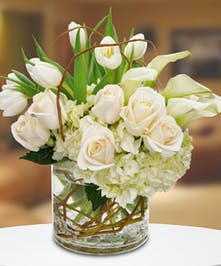 An elegant all-white design featuring roses, callas, tulips and hydrangeas