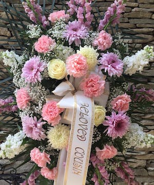 Pink, lavendar and white flowers are arranged in this beautiful spray