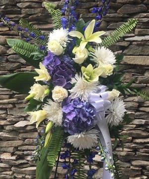 Blue and white flowers are displayed to create this beautiful spray