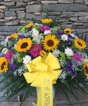 Mixed flowers are displayed in this traditional funeral basket