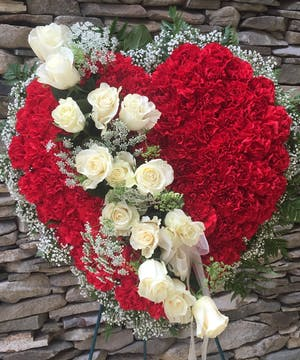 Red carnations fill this heart with a break of the purest white roses