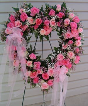 Open Heart displayed on a easel displayed with various colors of pink roses
