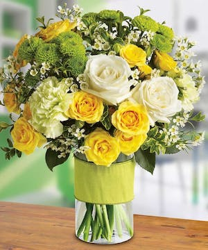 An elegant array of white and yellow roses and other favorites.